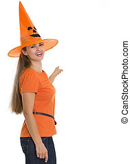 Happy young woman in Halloween hat pointing on back