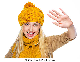 Happy young woman in hat and scarf greeting