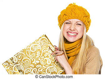 Happy young woman in hat and scarf with shopping bag