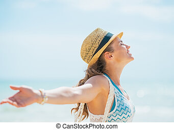 Happy young woman in hat and with bag rejoicing on beach