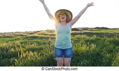 Happy young woman in hat enjoying summer in green field at sunset