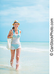 Happy young woman in hat with bag walking on sea coast
