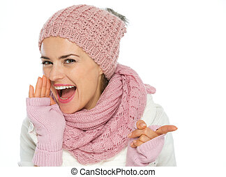 Happy young woman in knit winter clothing pointing on copy space