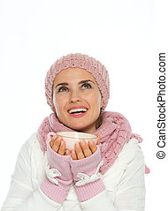 Happy young woman in knit winter holding cup and looking up on copy space
