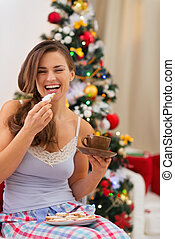 Happy young woman in pajamas eating cookies with hot chocolate near Christmas tree