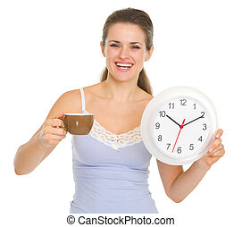 Happy young woman in pajamas with cup of coffee and clock