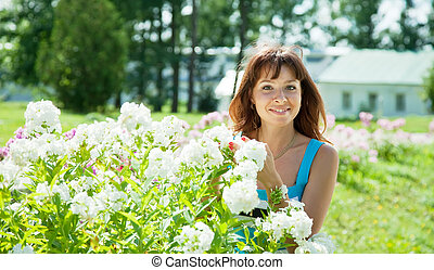 Happy young woman in   phlox plant