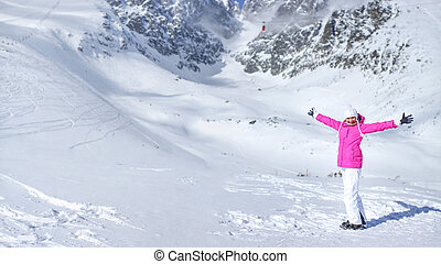 Happy young woman in pink ski jacket, gloves, hat and ski boots in front of snow covered mountain holding her hands spread out on a sunny day.