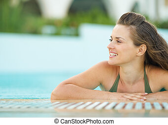 Happy young woman in pool looking on copy space