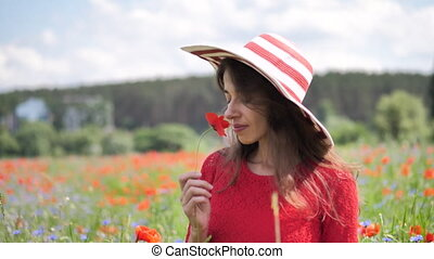 Happy young woman in red dress and big hat Enjoying Nature. Beauty Girl Outdoor walks on a poppy field. Freedom concept. Beauty Girl over Sky and Sun.