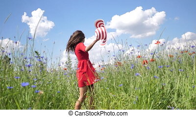 Happy young woman in red dress and big hat Enjoying Nature. Slow motion HD video Beauty Girl Outdoor walks on a poppy field. Freedom concept. Beauty Girl over Sky and Sun.