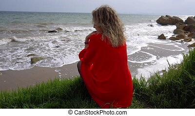 Happy Young Woman in Red Dress Have Fun at the Sea Coast and Sitting on the Cliff