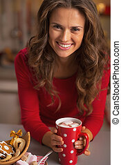 Happy young woman in red dress having christmas snack