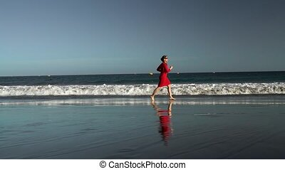Happy young woman in red dress runs along the ocean beach at sunset. Concept of carefree modern life.