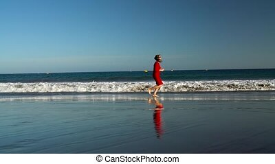 Happy young woman in red dress runs along the ocean beach at sunset. Concept of carefree modern life. Slow motion