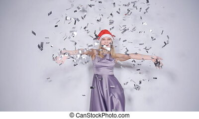 Happy young woman in Santa hat at celebration party with confetti falling