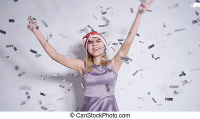 Happy young woman in Santa hat at celebration party with...