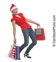 Happy young woman in Santa hat holding heavy shopping bags