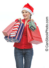 Happy young woman in Santa hat holding shopping bags