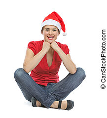 Happy young woman in Santa hat sitting on floor