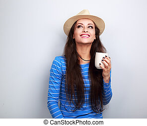 Happy young woman in straw hat drinking coffee with thinking face looking up on blue background