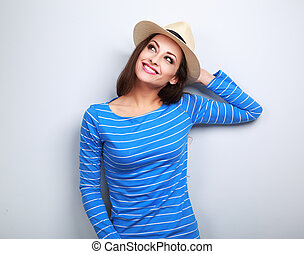 Happy young woman in straw hat thinking and looking up on blue background