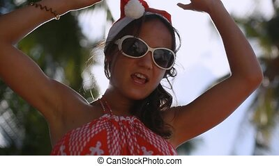 Happy young woman in sunglasses and christmas hat enjoying the sun in tropical island.
