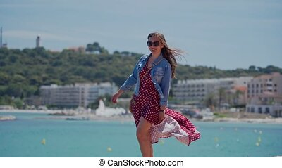 Happy young woman in sunglasses, romantic red dress and denim jacket is walking on stone wall of the embankment of the Mediterranean Sea on spring sunny day