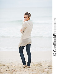 Happy young woman in sweater on beach