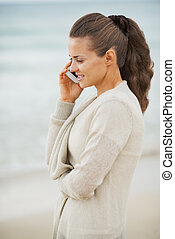 Happy young woman in sweater on beach talking mobile phone