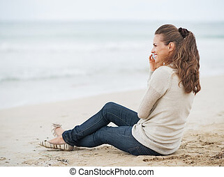Happy young woman in sweater sitting on lonely beach and talking mobile phone