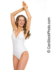 Happy young woman in swimsuit dancing