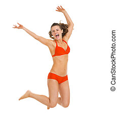 Happy young woman in swimsuit jumping
