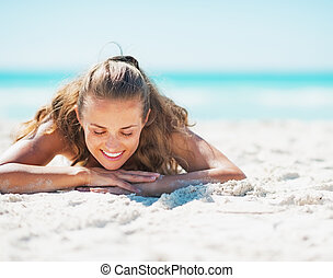 Happy young woman in swimsuit laying on beach