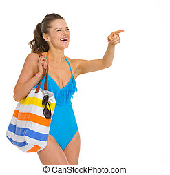 Happy young woman in swimsuit pointing on copy space