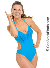 Happy young woman in swimsuit pointing up on copy space