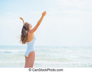 Happy young woman in swimsuit rejoicing on sea shore