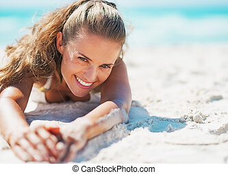 Happy young woman in swimsuit relaxing on beach