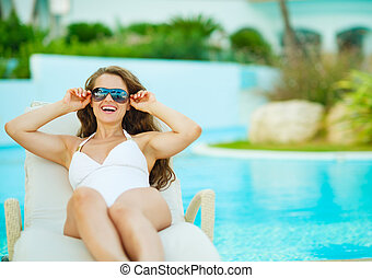Happy young woman in swimsuit relaxing on chaise-lounge