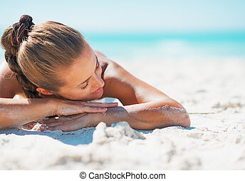Happy young woman in swimsuit relaxing while laying on sandy beach
