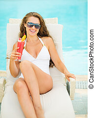 Happy young woman in swimsuit relaxing with cocktail on chaise-longue