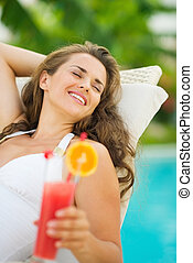 Happy young woman in swimsuit relaxing with cocktail on chaise-lounge