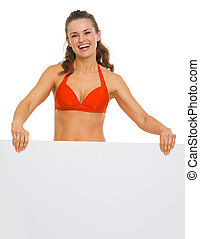 Happy young woman in swimsuit showing blank billboard