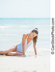 Happy young woman in swimsuit sitting on beach