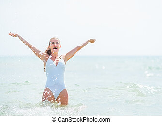 Happy young woman in swimsuit standing in sea and rejoicing