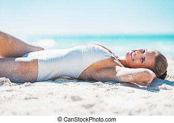 Happy young woman in swimsuit sunbathing on sandy beach