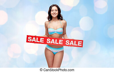 happy young woman in swimsuit with red sale sign - people,...