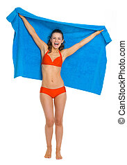 Happy young woman in swimsuit with towel
