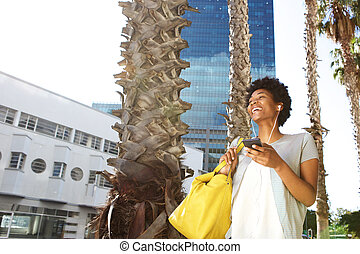 Happy young woman in the city listening music on mobile phone