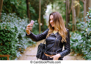 Happy young woman in trendy outfit smiling and taking selfie while standing on blurred back ground of park trees